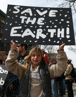 """Photo of a girl hold a """"Save the Earth"""" sign"""
