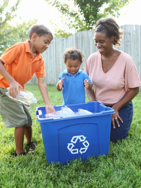 Photo of a family placing items in a recycling bin.